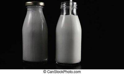 Two milk bottles on a black background. Slow motion