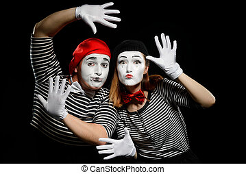 Two mimes leaning on imaginary wall with hands in white gloves