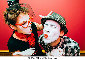 two mimes posing against a red wall background - two mimes...