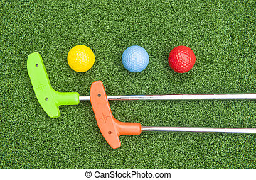 Two Mini Golf Putters and Three Balls