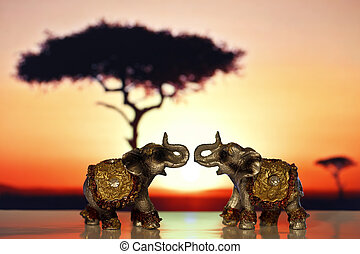 Two miniature elephant at sunset
