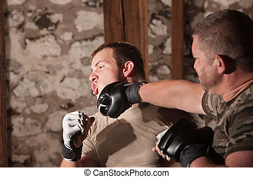 Two Mixed Martial Artists Sparring - Blond male fighter...