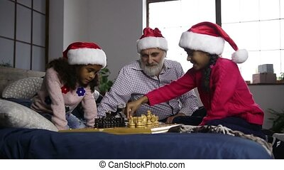 Two mixed race sisters playing chess on xmas eve