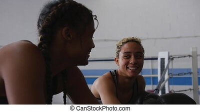 Two mixed race women discussing in boxing ring