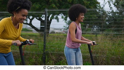 Two mixed race women riding electric scooter - Side view of ...