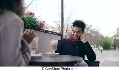 Two mixed race women sitting at the table in the street cafe, using smart phones and talking