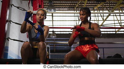 Two mixed race women wrapping their hands