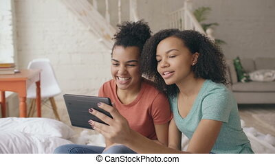 Two mixed race young funny girls talking on skype on tablet computer with their parents at home