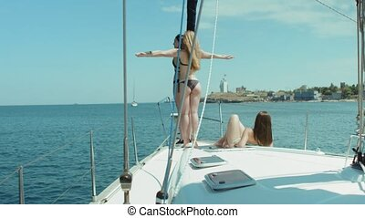 Two models in bikini hugging while standing on the bow of the yacht