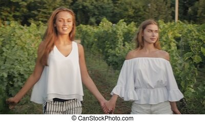 Two models walk through the green vineyard holding hands
