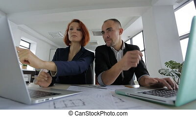 Two modern audience sitting in front of their laptops, talking and working in a large bright spacious office with panoramic windows with green plants. aged man and woman with red hair wearing jackets, white-collar workers, and today's powerful notebook computers are on the table paper for real ...