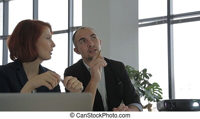 two modern employee sitting next to the projector at a business meeting, talking and working.