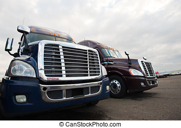 Two modern semi trucks on truck stop grills front view
