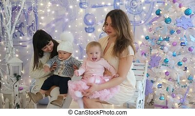 Two mom with little boy and girl sitting on a bench in Christmas studio