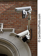 two monitoring cameras for surveillance on a wall