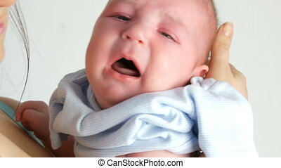 Two month old newborn baby cries loudly. Child face close up...