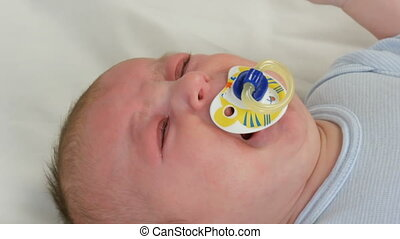 Two month old newborn baby cries loudly with pacifier in...