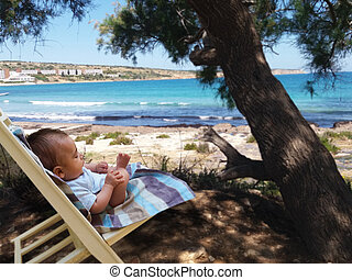 two months old baby boy on the beach