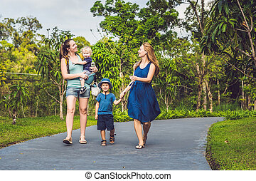 two mothers and two children are walking in the park