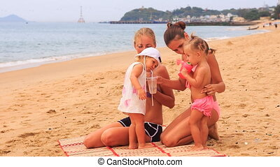 two mothers little daughters sit on mat drink beverages