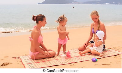 two mothers little daughters sit on mat and play