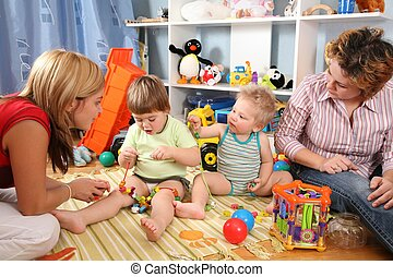 two mothers play with children in playroom 2