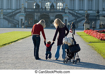 two mothers walking a baby