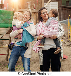 Two mothers with babies in baby carriers warp