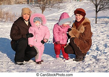 two mothers with children outdoor in winter