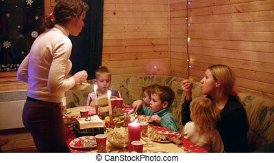 Two mothers with four children sit at festive table