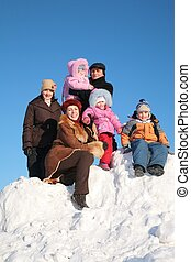 two mothers with grandfather and children on snow hill