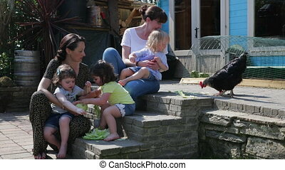 Two mothers with their daughters feeding the chickens - Two...