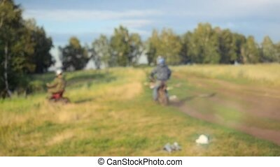 Two motorcyclists on bike going to the forest on road in field. Summer time. Blurred background