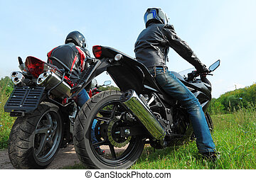 two motorcyclists standing on country road, back view