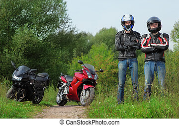 two motorcyclists standing on country road near bikes