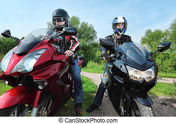 two motorcyclists standing on country road