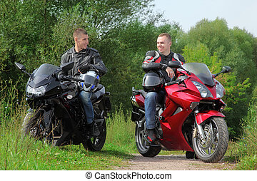 two motorcyclists standing on country road, without helmets