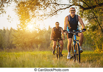 Two mountain bikers riding bike in the forest