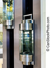 Two moving modern elevators in shopping centre.