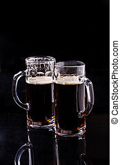 Two mugs of dark beer