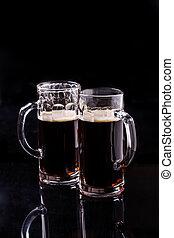 Two mugs of dark beer