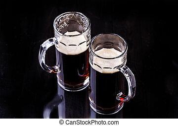 Two mugs of foamy beer