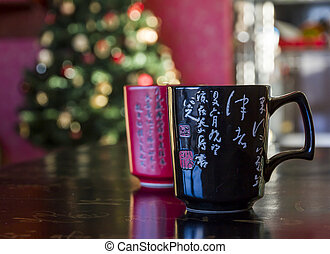 Two mugs red and black decorated with chinese calligraphy, lying on black chinese table likewise decorated with calligraphy signs with blurred christmas tree in background
