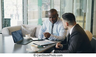 Two multi-ethnic businessmen looking at diagrams and graphs on laptop screen and discussing the financial report of their startup in modern cafe during lunch time.