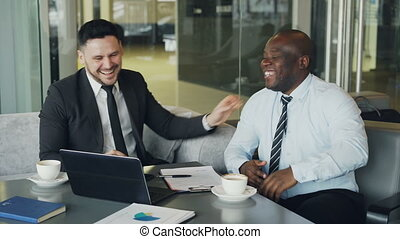 Two multi ethnic businessmen looking at laptop computer and laughing in glassy cafe. African American businessman and Caucasian colleagues having fun and joking