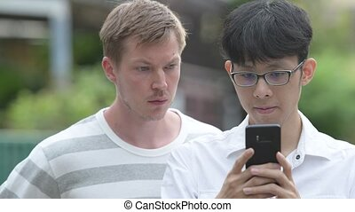 Two multi-ethnic businessmen using phone together in the...