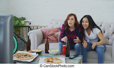 Two multi-ethnic female friends watching sports match on TV together at home while drinking beer and eating snacks