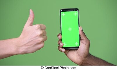 Two multi-ethnic hands showing phone while giving thumbs up...