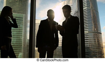 Two multicultural businessmen talking and handshaking,...