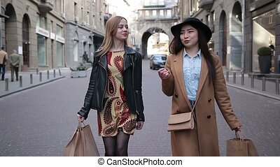 Two multiethnic girlfriends shopping together